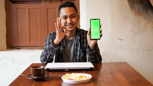 Asiatischer geschäftsmann, der grünen bildschirm des telefons am café spielt