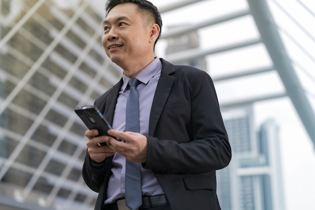 Asiatischer geschäftsmann, der handy mit geschäftslokalgebäuden in der stadt steht und hält