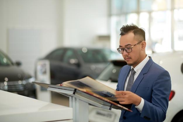 Asiatischer geschäftsmann, der im autohausausstellungsraum steht und durch album schaut