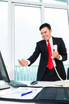 Asiatischer geschäftsmann, der im büro telefoniert, das gewinn steuert