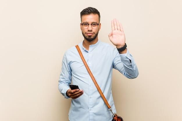 Asiatischer geschäftsmann der jungen mischrasse, der ein telefon steht mit der ausgestreckten hand zeigt stoppschild hält