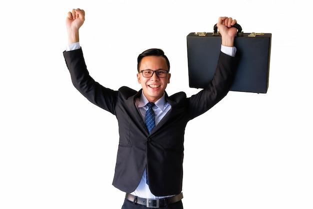 Asiatischer geschäftsmann, der koffer hält und seine hände mit lächelndem gesicht anhebt