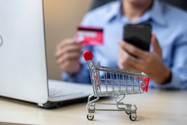 Asiatischer geschäftsmann, der kreditkarte unter verwendung des laptops und des intelligenten telefons hält