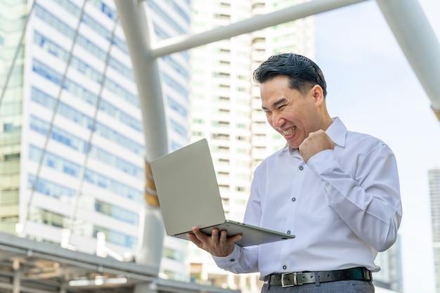 Asiatischer geschäftsmann, der laptop-computer auf geschäftsviertel-stadt - lebensstil-geschäftsmannkonzept verwendet