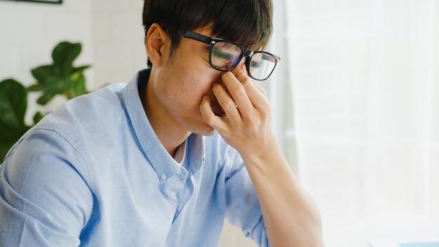 Asiatischer geschäftsmann, der laptop verwendet, der über arbeit verärgert ist, papiere zerreißt und im wohnzimmer zu hause schreit. arbeiten von zu hause aus, fernarbeit, soziale distanzierung, quarantäne zur vorbeugung von koronaviren.