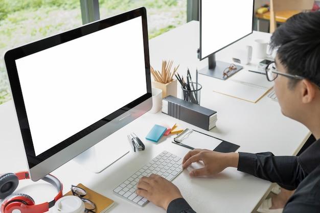 Asiatischer geschäftsmann, der mit computer im modernen büro arbeitet.