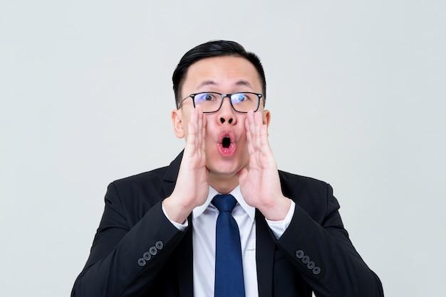 Asiatischer geschäftsmann, der mit den händen schreit, die um mund schalen