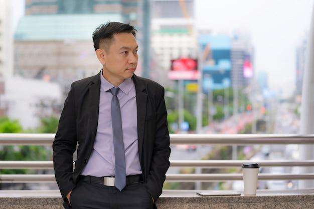 Asiatischer geschäftsmann, der mit geschäftslokalgebäuden in der stadt steht