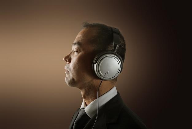 Asiatischer geschäftsmann, der musik auf kopfhörern hört