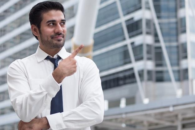 Asiatischer geschäftsmann, der oben zeigt; porträt eines asiatischen, nordindischen erfolgreichen und selbstbewussten geschäftsmanns zeigt mit dem finger nach oben