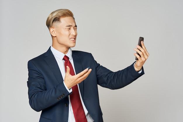 Asiatischer geschäftsmann, der sein smartphone frustriert schaut