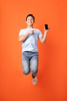 Asiatischer geschäftsmann, der smartphone springt und hält