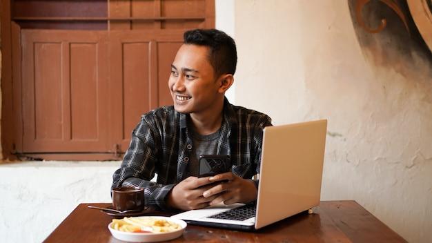 Asiatischer geschäftsmann, der telefon am café spielt