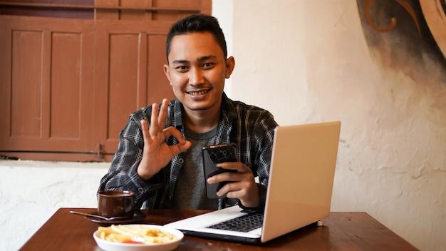 Asiatischer geschäftsmann, der telefon an der geste des cafés ok spielt