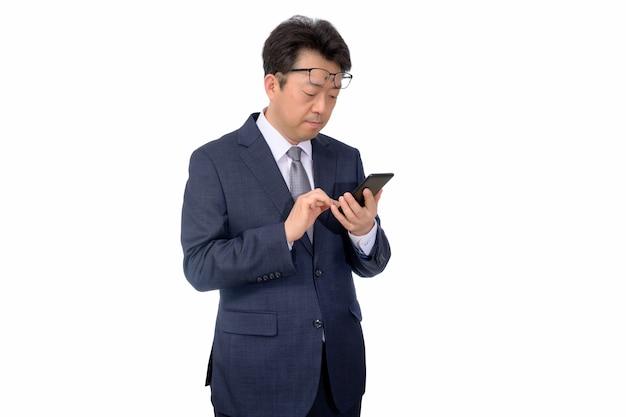 Asiatischer geschäftsmann, der versucht, etwas an seinem handy zu lesen. schlechte sicht, presbyopie, myopie.