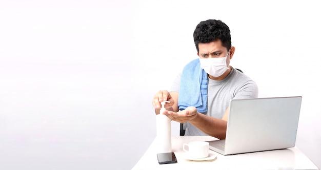 Asiatischer geschäftsmann, der von zu hause aus schutzmaske trägt. in quarantäne für coronavirus, das schutzmaske trägt. von zu hause aus arbeiten. reinigung seiner hände mit alkoholgel. mit kopierraum.