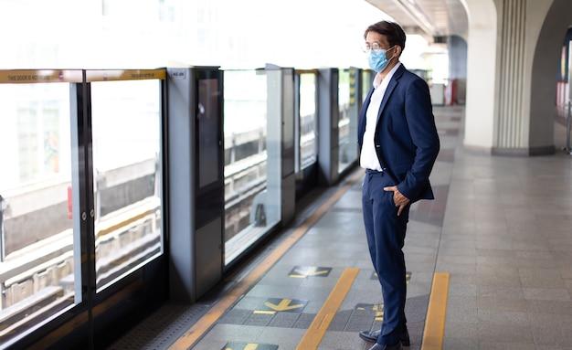 Asiatischer geschäftsmann, der während der covid-19-pandemie gesichtsmasken trägt, während er mit öffentlichen verkehrsmitteln fährt.