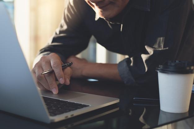 Asiatischer geschäftsmann, der zu hause am laptop arbeitet