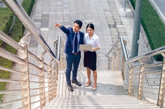 Asiatischer geschäftsmann des managers, der ideen mit laptop-besprechung und gehender geschäftsfrau außerhalb bespricht.