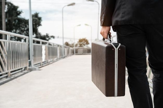 Asiatischer geschäftsmann gehen und tragen eine tasche, um sich für einen job zu bewerben. versagens- und entlassungskonzept für die krankheit covid-19 und arbeitslose.
