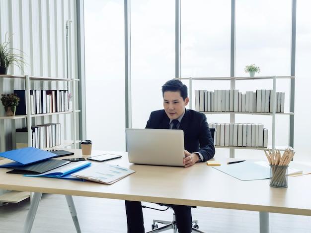 Asiatischer geschäftsmann im anzug, der am tisch sitzt und am laptop im büro arbeitet