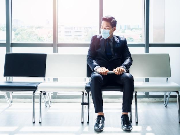 Asiatischer geschäftsmann im anzug, der schützende gesichtsmaske trägt, die mit seinem lebenslauf auf seinem schoß sitzt und auf vorstellungsgespräch wartet