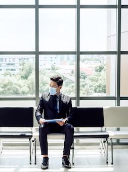 Asiatischer geschäftsmann im anzug, der schützende gesichtsmaske trägt und seinen lebenslauf liest und auf vorstellungsgespräch nahe vertikalem stil des riesigen glasfensters wartet