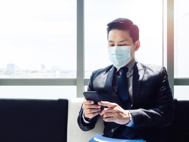 Asiatischer geschäftsmann im anzug, der schützende gesichtsmaske trägt und smartphone verwendet, während in modernem bürogebäude nahe riesigem glasfenster sitzen