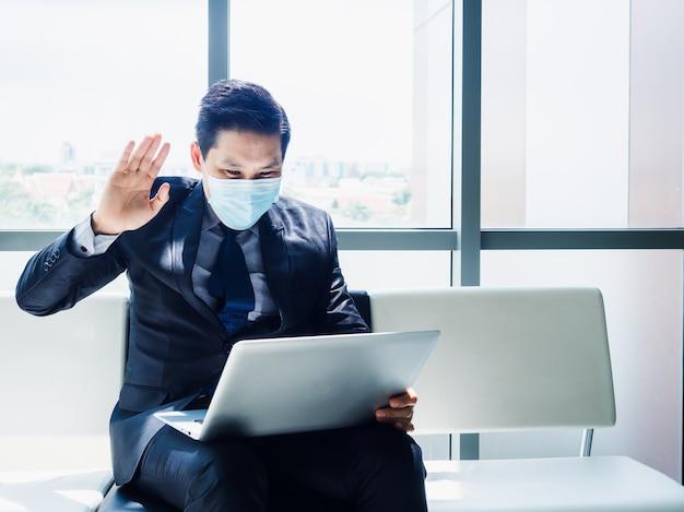 Asiatischer geschäftsmann im anzug, der schützende gesichtsmaske trägt, winkte, um kollegen im laptop-monitor auf seinem schoß zu begrüßen
