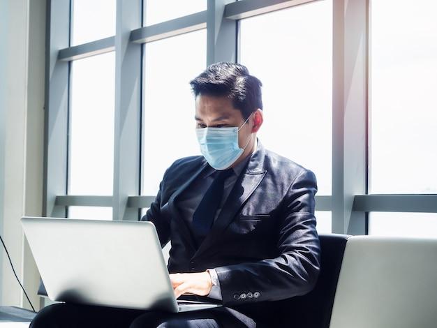 Asiatischer geschäftsmann im anzug, der schützende gesichtsmaske unter verwendung des laptop-computers auf seinem schoß trägt, während im modernen bürogebäude nahe riesigem glasfenster sitzt