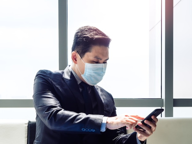 Asiatischer geschäftsmann im anzug, der schützende gesichtsmaske unter verwendung des mobiltelefons beim sitzen im modernen bürogebäude nahe dem riesigen glasfenster trägt.