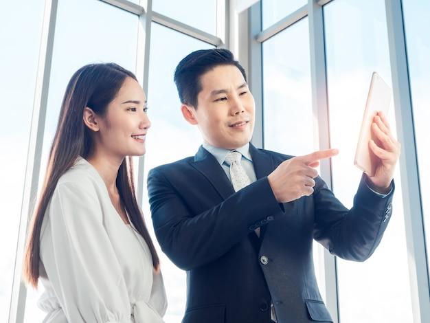 Asiatischer geschäftsmann im anzug und junge frau, die videoanruf mit digitalem tablett auf glasfenster machen