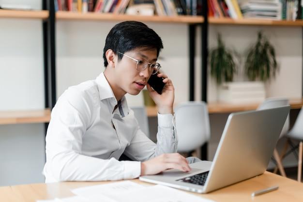 Asiatischer geschäftsmann im büro arbeitet mit laptop