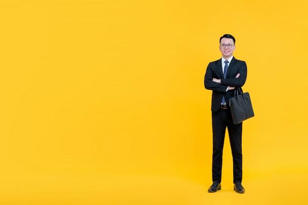 Asiatischer geschäftsmann im formalen anzug, der mit den armen steht, kreuzte das halten des aktenkoffers