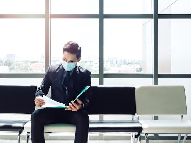 Asiatischer geschäftsmann im schwarzen anzug, der schützende gesichtsmaske trägt und seinen lebenslauf überprüft und auf vorstellungsgespräch nahe riesigem glasfenster wartet
