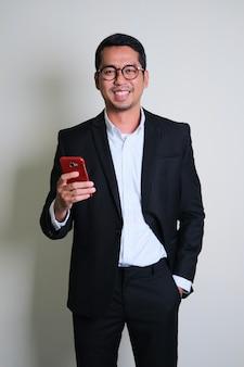 Asiatischer geschäftsmann im schwarzen anzug, der selbstbewusst lächelt, während er sein smartphone hält