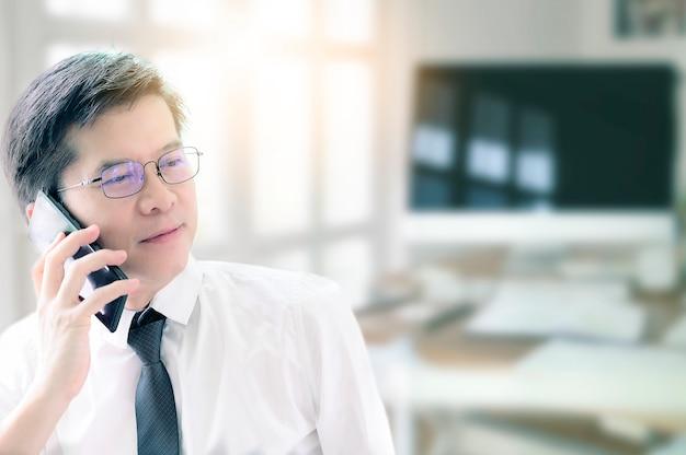 Asiatischer geschäftsmann im weißen hemd mit gläsern unter verwendung des handys im büro.