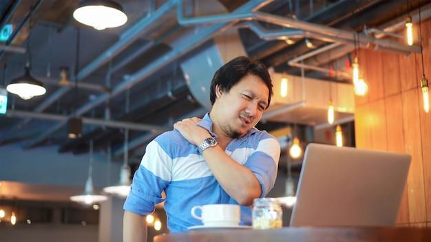Asiatischer geschäftsmann in der zufälligen klagenfunktion, die symptom haben, ist nackenschmerzen, rückenschmerzen, headac