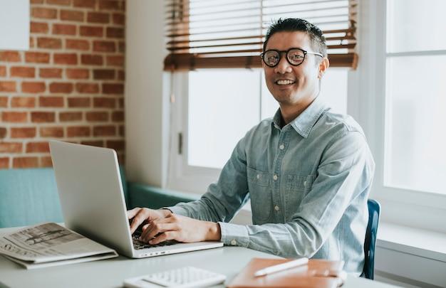 Asiatischer geschäftsmann in einem büro mit einem laptop