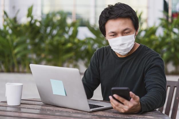 Asiatischer geschäftsmann in freizeitkleidung, der zu hause mit dem handy arbeitet