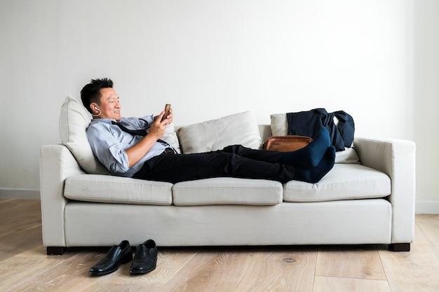 Asiatischer geschäftsmann macht pause und liegt auf der couch