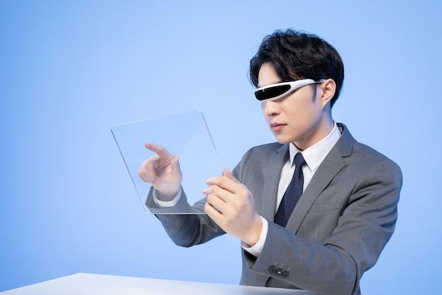 Asiatischer geschäftsmann mit brille, die einen bildschirm berührt