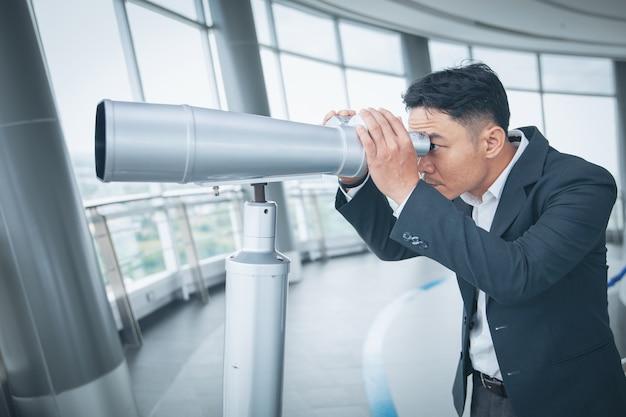 Asiatischer geschäftsmann mit dem fernglas an der spitze des gebäudes