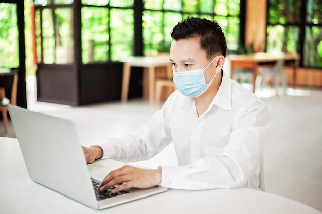 Asiatischer geschäftsmann mit den schwarzen haaren, die eine gesichtsmaske für die kovid 19 schutzkoronagrippe im modernen büro tragen, er arbeitet mit laptop zwischen saisonalen viruserkrankungen.