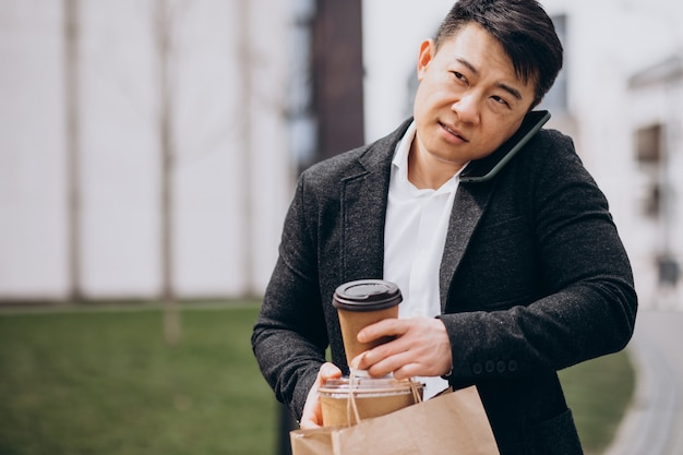 Asiatischer geschäftsmann mit essen zum mitnehmen, am telefon sprechend