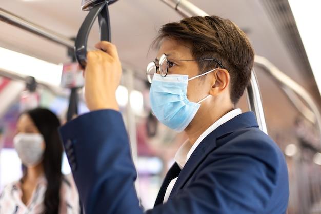 Asiatischer geschäftsmann mit gesichtsmasken beim pendeln mit öffentlichen verkehrsmitteln während der covid-19-pandemie.