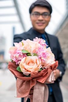 Asiatischer geschäftsmann mit rosenstrauß für glückwünsche