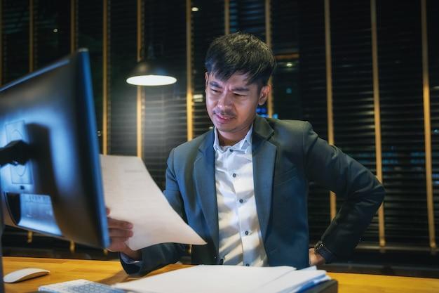 Asiatischer geschäftsmann mit rückenschmerzen ein büro. schmerzlinderung konzept
