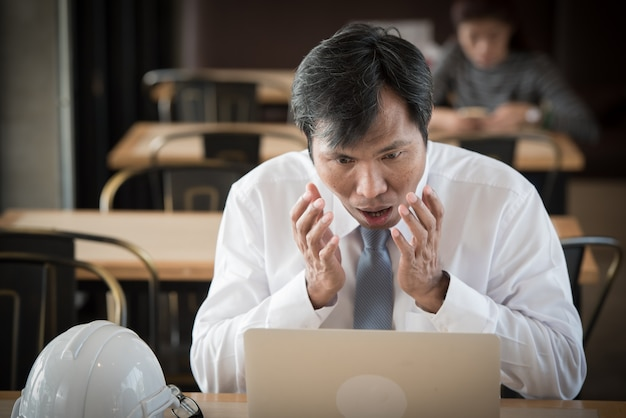 Asiatischer geschäftsmann mit überraschungsgesicht vor laptop-computer.