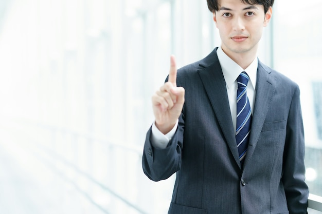 Asiatischer geschäftsmann posiert mit seinem zeigefinger nach oben